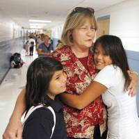 Photo - School principal Dot Violett getting hugs in the hallway from sixth graders Rhonda Esculera and Cristina Delgado, both age 11, before classes start for the day at Adams Elementary in Oklahoma City Wednesday, Aug. 1, 2012. Wednesday was the first day of classes in the Oklahoma City Public School District.  Photo by Paul B. Southerland, The Oklahoman