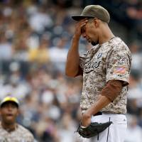 Photo - San Diego Padres starting pitcher Tyson Ross wipes his brow after surrendering a run to the Atlanta Braves in the seventh inning of a baseball game Sunday, Aug. 3, 2014, in San Diego. (AP Photo/Lenny Ignelzi)