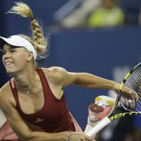 Photo - Caroline Wozniacki, of Denmark, follows through on a serve to Sara Errani, of Italy, during the quarterfinals of the U.S. Open tennis tournament, Tuesday, Sept. 2, 2014, in New York. (AP Photo/Charles Krupa)