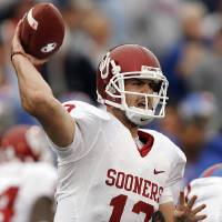 Photo - Oklahoma Landry Jones (12) throws a pass against Kansas during the second half of the college football game between the University of Oklahoma Sooners (OU) and the University of Kansas Jayhawks (KU) on Saturday, Oct. 24, 2009, in Lawrence, Kan. Oklahoma won the game 35-13. Photo by Chris Landsberger, The Oklahoman ORG XMIT: KOD