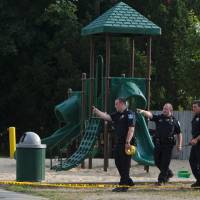 Photo - Kentwood police investigate a stabbing that occurred in a playground in Pinebrook Village, in Kentwood, Mich., on  Aug. 4, 2014.   Police say a 12-year-old boy has stabbed a 9-year-old boy at the playground in western Michigan, sending the child to a hospital.   Police also didn't immediately release detail on the condition of the wounded child. The older boy was taken into custody for questioning by police. (AP Photo/The Grand Rapids Press, Joel Bissell) ALL LOCAL TELEVISION OUT; LOCAL TELEVISION INTERNET OUT