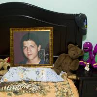 Photo -   CORRECTS LAST NAME SPELLING AND ADDS FIRST NAME 'EBED' - In this Oct 17, 2012 photo, an image of late Ebed Jaasiel Yanes, 15, sits on his bed at his parent's home in Tegucigalpa, Honduras. According to his relatives, Yanes was killed by soldiers early Sunday, May 27, when he was riding a motorcycle near a military checkpoint. (AP Photo/Esteban Felix)