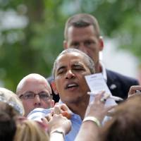 Photo - President Barack Obama makes his way through the crowd after he held a town hall meeting at Minnehaha Park ,Thursday, June 26, 2014, in Minneapolis. Obama said that Washington needs to stop