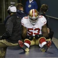 Photo - San Francisco 49ers' NaVorro Bowman is taken to the locker room on a cart after injuring his leg during the second half of the NFL football NFC Championship game against the Seattle Seahawks, Sunday, Jan. 19, 2014, in Seattle. (AP Photo/Marcio Jose Sanchez)