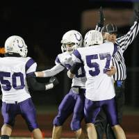 Photo - Bethany's Gage Diffee (20), middle, celebrates with teammates Michael Paul (50) and Brett Gilstrap (57) after Diffee scored in the first quarter during the Class 3A high school football semifinal playoff  game between Heritage Hall and Bethany at Putnam City High School in Oklahoma City, Saturday, December 4, 2010. Photo by Nate Billings, The Oklahoman