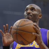 Photo - Los Angeles Lakers guard Kobe Bryant reacts during the first half of their NBA basketball game against the Los Angeles Clippers, Friday, Jan. 4, 2013, in Los Angeles.  (AP Photo/Mark J. Terrill)