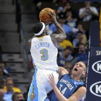 Photo - Denver Nuggets guard Ty Lawson, left, collides with Minnesota Timberwolves center Greg Stiemsma, right, in the first quarter of an NBA basketball game on Saturday, March 9, 2013, in Denver.  (AP Photo/Chris Schneider)