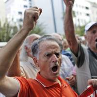 Photo -   A pensioner shouts slogans during an anti-austerity protest in front of the EU headquarters in Athens on Monday, Oct. 8, 2012. The 17 eurozone ministers will look Monday at Greece's budget proposals. They will hear from the troika — the European Commission, the European Central Bank and the International Monetary Fund — about its negotiations with the Greek government. No final troika report will be submitted, so no decision on a new payout of aid will be made.(AP Photo)