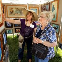 Photo - Artist Kathy Morrow shows her work to Louise Lazalier at the annual May Fair Festival Saturday at Andrews Park in Norman. PHOTO BY STEVE SISNEY, THE OKLAHOMAN  STEVE SISNEY