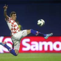 Photo - FILE - In this June 7, 2013, file photo, Croatia's Mario Mandzukic kicks the ball during the group A World Cup qualifying soccer match between Croatia and Scotland, in Zagreb, Croatia. Mandzukic, who was red-carded in a decisive qualifier against Iceland will have his suspension carried over from qualifying so he will have to sit out against the hosts. (AP Photo/Darko Bandic,File)