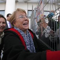 Photo - Chile's former president Michelle Bachelet greets supporters and journalists upon her arrival at the Arturo Merino Benitez Internationl Airport in Santiago, Chile, Wednesday, March 27, 2013. Bachelet has returned to the South American country after ending a two-year stint heading the U.N. women's agency in New York. She landed in the capital Wednesday amid wide speculation she'll run for president again this year. Pictured behind Bachelet is Santiago Mayor Carolina Toha. (AP Photo/Luis Hidalgo)