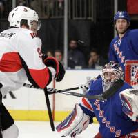 Photo -   New York Rangers goalie Henrik Lundqvist, bottom right, of Sweden, and Ottawa Senators' Milan Michalek, left, of the Czech Republic, compete for the puck as it goes up in the air in front of the net during the first period of Game 7 of a first-round NHL hockey Stanley Cup playoff series on Thursday, April 26, 2012, in New York. Rangers' Dan Girardi (5) looks on. (AP Photo/Julio Cortez)