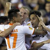 Photo - Valencia's  Jonas Gonzalves from Brazil, right, and Eduardo Vargas from Chile, left, Jeremy Mathieu from France, center, celebrates after scoring against Sevilla during their Europa League semifinal second leg soccer match at the Mestalla stadium in Valencia, Spain, Thursday, May 1, 2014. (AP Photo/Alberto Saiz)