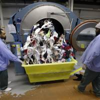 Photo - Inmates look on as bras being laundered as part of a breast cancer awareness campaign fall out of a washing machine at Central Maryland Correctional Facility in Sykesville, Md., Thursday, Dec.13, 2012. Nearly 10,000 bras were expected to be laundered by the inmates after they were collected by a radio station in Frederick, Md. One dollar for each bra was donated to breast cancer research, and the cleaned bras were expected to be donated to local women's shelters. Inmates at the facility annually handle more than 2.2 million pounds of laundry from state agencies and non-profit organizations in Maryland. (AP Photo/Patrick Semansky)