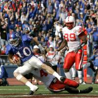 Photo - COLLEGE FOOTBALL: Kansas' Kerry Meier (10) is pulled down by Nebraska safety Adam Watson (4) after Meier caught a pass in the end zone for a touchdown during the first quarter of a football game Saturday, Nov. 3, 2007, in Lawrence, Kan. (AP Photo/Charlie Riedel)  ORG XMIT: KSCR103 ORG XMIT: OKC0711031413002801 ORG XMIT: 0711062205220523