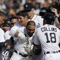 Photo - Detroit Tigers' Alex Gonzalez, center, is mobbed after hitting the game winning single to score the winning run from third during the ninth inning of a baseball game against the Kansas City Royals in Detroit, Monday, March 31, 2014. (AP Photo/Carlos Osorio)