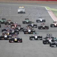 Photo - The pack led by Germany's Nico Rosberg of Mercedes, bottom left, races into the first corner during the British Formula 1 Grand Prix at Silverstone circuit, Silverstone, England, Sunday, July 6, 2014. The British Grand Prix was halted on the opening lap Sunday after a collision involving Raikkonen and Felipe Massa of Williams. Massa escaped unhurt and drove back to the pits without his left rear wheel, but Raikkonen emerged limping from his smashed Ferrari that had lost most of the front end and left rear wheel. The race was stopped as 2007 champion Raikkonen was taken to the circuit medical center. He appears to have lost control of his car and hit the barriers before spinning across the track where he collided with Massa. The race will resume once debris from the crash is cleared and damage to track barriers is repaired. (AP Photo/Lefteris Pitarakis)