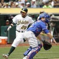 Photo - Oakland Athletics' Eric Sogard, left, comes in to score the A's first run as New York Mets catcher Travis d'Arnaud, right, waits for the throw during the third inning of their interleague baseball game Wednesday, Aug. 20, 2014, in Oakland, Calif. Sogard after the Athletics' Coco Crisp doubled. (AP Photo/Eric Risberg)