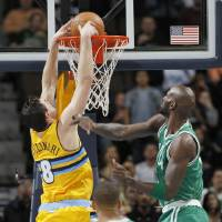 Photo - Denver Nuggets forward Danilo Gallinari, of Italy, drops the ball in for a basket as Boston Celtics forward Kevin Garnet, right, and guard Avery Bradley watch during the first quarter of an NBA basketball game in Denver on Tuesday, Feb. 19, 2013. (AP Photo/David Zalubowski)