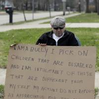Photo - Edmond Aviv sits on a street corner holding a sign Sunday, April 13, 2014, in South Euclid, Ohio declaring he's a bully, a requirement of his sentence because he was accused of harassing a neighbor and her disabled children for the past 15 years.  Municipal Court Judge Gayle Williams-Byers ordered Aviv, 62,  to display the sign for five hours Sunday. It says: