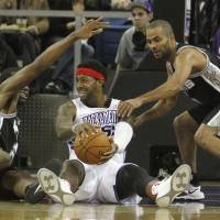 Photo -   Sacramento Kings forward James Johnson, center, tries to protect the ball from San Antonio Spurs forward Kawhi Leonard, left, and Tony Parker during the first quarter of an NBA basketball game in Sacramento, Calif., Friday, Nov. 9, 2012. (AP Photo/Rich Pedroncelli)