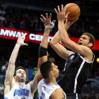 Photo -   Brooklyn Nets center Brook Lopez, right, goes up for a shot in front of Orlando Magic guard J.J. Redick (7) and Gustavo Ayon, (19), of Mexico, during the first half of an NBA basketball game in Orlando, Fla., Friday, Nov. 9, 2012.(AP Photo/Phelan M. Ebenhack)