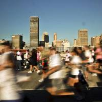 Photo - Runners are a blur as they pass the downtown skyline during the 2010 Susan G. Komen Central Oklahoma Race for the Cure in downtown Oklahoma City on Saturday, Oct. 9, 2010, in Oklahoma City, Okla.  Photo by Chris Landsberger, The Oklahoman ORG XMIT: KOD