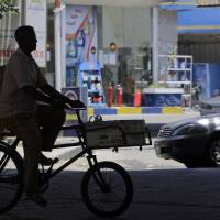 Photo - An Egyptian rides his bicycle past a gasoline station in Cairo, Egypt, Saturday, July 5, 2014. Egypt's government raised the prices of fuel by up to 78 percent starting Saturday, following on a promise to cut subsidies that eat up nearly a quarter of the state budget, the official news agency reported. The country's successive leaders have balked at reducing them because half of the country's 85 million people live at or below the poverty line of $2 a day and rely on government subsidies of wheat and fuel for survival. (AP Photo/Amr Nabil)
