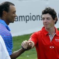Photo -   Tiger Woods, left, and Rory McIlroy of Northern Ireland, shake after the first round of the BMW Championship PGA golf tournament at Crooked Stick Golf Club in Carmel, Ind., Thursday, Sept. 6, 2012. (AP Photo/Charles Rex Arbogast)
