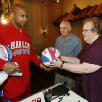 Photo - Harlem Globetrotter player Flight Time Lang gives an autographed basketball to George and Lin Wilson. Flight Time surprised Lin Wilson during a lunch date with her husband at Zio's in Bricktown.