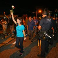 Photo - A protester holds roses in the air as she marches with others past police officers in Ferguson, Mo. on Tuesday, Aug. 19, 2014. On Saturday, Aug. 9, 2014, a white police officer fatally shot Michael Brown, an unarmed black teenager, in the St. Louis suburb. (AP Photo/Atlanta Journal-Constitution, Curtis Compton)