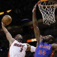 Photo - Miami Heat guard Dwyane Wade (3) goes up for a shot against Detroit Pistons forward Jason Maxiell (54) during the first half of an NBA basketball game, Friday, Jan. 25, 2013, in Miami. (AP Photo/Wilfredo Lee)