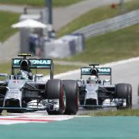 Photo - Mercedes driver Nico Rosberg of Germany,  and Mercedes driver Lewis Hamilton of Britain  compete during the Austrian Formula One Grand Prix race at the Red Bull Ring in Spielberg, Austria, Sunday, June 22, 2014.  (AP Photo/Darko Bandic)