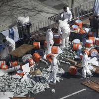 Photo - Investigators comb through the post finish line area of the Boston Marathon at Boylston Street, two days after two bombs exploded just before the finish line, Wednesday, April 17, 2013, in Boston. (AP Photo/Julio Cortez)