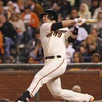 Photo - San Francisco Giants' Buster Posey hits a two RBI double against the Miami Marlins during the fifth inning of a baseball game, Thursday, May 15, 2014, in San Francisco. (AP Photo/George Nikitin)