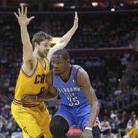 Photo - Oklahoma City Thunder's Kevin Durant (35) drives past Cleveland Cavaliers' Matthew Dellavedova (8), from Australia, during the first quarter of an NBA basketball game Thursday, March 20, 2014, in Cleveland. (AP Photo/Tony Dejak)