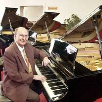 Photo - The late Albert Evans, owner of Albert Evans Piano Co., sits at a new piano in his store's showroom on N MacArthur Blvd. in this photo from 2002.  Photo by JIM BECKEL, The Oklahoman Archives