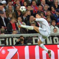 Photo - Real's Cristiano Ronaldo jumps for the ball during the Champions League semifinal second leg soccer match between Bayern Munich and Real Madrid at the Allianz Arena in Munich, southern Germany, Tuesday, April 29, 2014. (AP Photo/Kerstin Joensson)