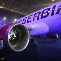 "Photo - New cabin crew members stand by the first Airbus A319-100 aircraft in Air Serbia livery parked in a hangar during the inauguration ceremony at Belgrade's Nikola Tesla Airport, Serbia, Friday, Oct. 25, 2013. Officials say that Air Serbia, Balkan country's new national carrier partly owned by Etihad Airways, formally starts flying this weekend, spelling the end for the old loss-making JAT Airways. Air Serbia's chief manager Dane Kondic said Friday that the company's inaugural flight will take place on Saturday to Abu Dhabi, United Arab Emirates. He says that ""it is an important flight that will mark a crossroads."" Kondic and Serbia's deputy prime minister Aleksandar Vucic unveiled at a ceremony at Belgrade's airport an Airbus A319 plane bearing a double-headed eagle logo in Serbia's national, red, white and blue colors. Vucic says Air Serbia hopes to become the leading regional airline. (AP Photo/Darko Vojinovic)"