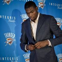 Photo - NBA BASKETBALL PLAYER: Oklahoma City Thunder's Kevin Durant buttons his jacket as he leaves the stage after a press conference to officially announce Durant's  five-year contract extension to play for the Oklahoma City Thunder on Friday, July 9, 2010, in Oklahoma City, Okla.   Photo by Chris Landsberger, The Oklahoman ORG XMIT: KOD