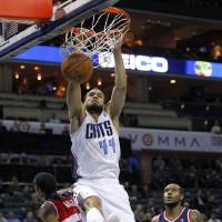 Photo -   Charlotte Bobcats' Jeffery Taylor (44) dunks over Washington Wizards' Trevor Ariza (1) and Trevor Booker (35) during the first half of an NBA basketball game in Charlotte, N.C., Tuesday, Nov. 13, 2012. (AP Photo/Chuck Burton)