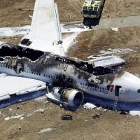 Photo - FILE - In this July 6, 2013 file aerial photo shows the wreckage of the Asiana Flight 214 airplane after it crashed at the San Francisco International Airport in San Francisco. A ban on video cameras by the  San Francisco fire department   now explicitly includes helmet-mounted ones filming emergency scenes, according to Chief Joanne Hayes-White. The edict comes after images taken in the aftermath of the July 6 Asiana Airlines crash at San Francisco International Airport were made public, leading to questions about first responders actions that resulted in a survivor being run over by a fire truck. (AP Photo/Marcio Jose Sanchez, File)