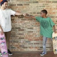 Photo - Matt Ramesh (left) celebrates with Moses Ward, age 11, of Edmond, after Ward landed a trick during a skate demonstration outside the Edmond Public Library in Edmond on Monday, July 12, 2010. Photo by John Clanton, The Oklahoman ORG XMIT: KOD