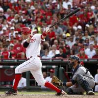 Photo - Cincinnati Reds' Todd Frazier, left, hits a sacrifice fly off Milwaukee Brewers starting pitcher Kyle Lohse scoring Brandon Phillips during the fourth inning of a baseball game, Sunday, May 4, 2014, in Cincinnati. Brewers catcher Jonathan Lucroy watches at right.  (AP Photo/David Kohl)