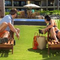 Photo - This image from video shows an image from a Kindle Paperwhite commercial featuring a young woman on a beach vacation lounging next to a  young man, waiting for their husbands, shown in the background at the bar. Welcome to the latest in gay imagery in mainstream advertising, where LGBT people have been waiting for a larger helping of fairness and accuracy, on screen and in print. Traditionally lagging behind TV and film content in terms of LGBT inclusion, advertisers in this country are suffering considerably less blowback for the effort. (AP Photo/Amazon)