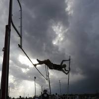Photo - A high school student pole vaults against threatening skies in Montgomery, Ala., Monday, March 18, 2013. The track meet at Montgomery Academy was cancelled as the state long weather front of severe thunderstorms approached. (AP Photo/Dave Martin)