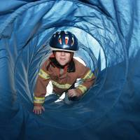 Photo - Zachery Duck, 7, climbs through a tunnel representing smoke during Edmond Fire Department's Children's Safety Challenge over spring break. PHOTO BY DAVID MCDANIEL, THE OKLAHOMAN