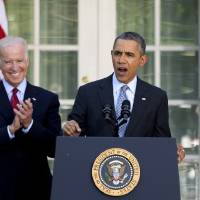 Photo - President Barack Obama, with Vice President Joe Biden, speaks in the Rose Garden of the White House in Washington, Tuesday, April 1, 2014, about the Affordable Care Act. The deadline to sign up for health insurance under the Affordable Care Act passed at midnight Monday night. (AP Photo/Carolyn Kaster)