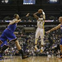 Photo - Indiana Pacers forward Paul George, center, shoots between New York Knicks defenders Tyson Chandler, left, and Jason Kidd during the second half of an NBA basketball game in Indianapolis, Wednesday, Feb. 20, 2013. The Pacers won 125-91. (AP Photo/AJ Mast)
