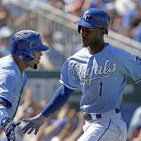 Photo - Kansas City Royals' Jarrod Dyson (1) celebrates with Emilio Bonifacio after scoring on a wild pitch thrown by Seattle Mariners starting pitcher Felix Hernandez during the fifth inning of a baseball game Monday, Sept. 2, 2013, in Kansas City, Mo. (AP Photo/Charlie Riedel)